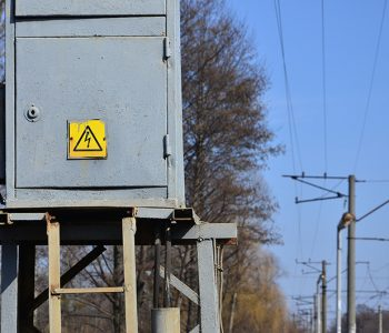 Electrical transformer in gray with a symbol warning of the danger of high voltage near the railway line. A small substation for the supply of electricity